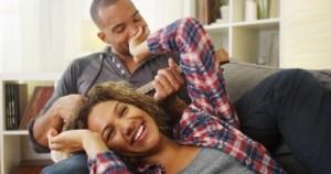 Happy black couple lying on couch with ukulele