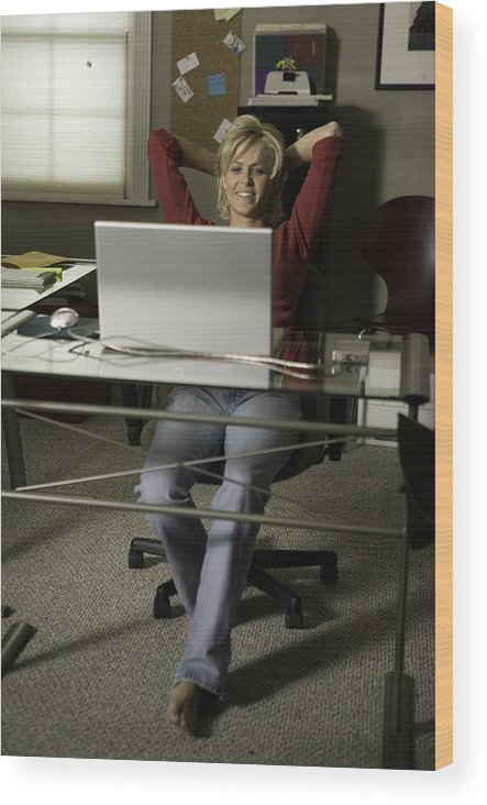 Woman Sitting Behind Desk In Office, Relaxing Wood Print by Photodisc