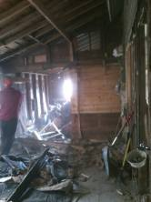 Here the wall is almost halfway, you can see the light of the wood shed windows shining across the mega nightmare that we have of clean up. The wood shed is, of course, also filled with wood that we're gonna have to take out.