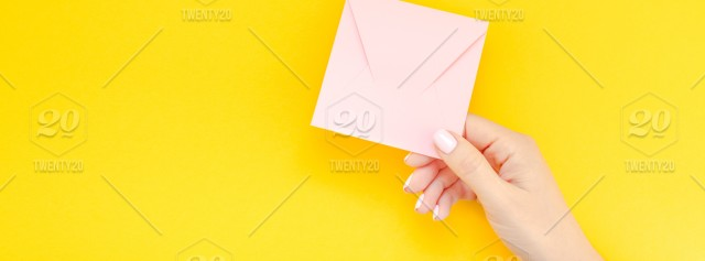 Woman hand with pastel manicure holding small love millennial pink