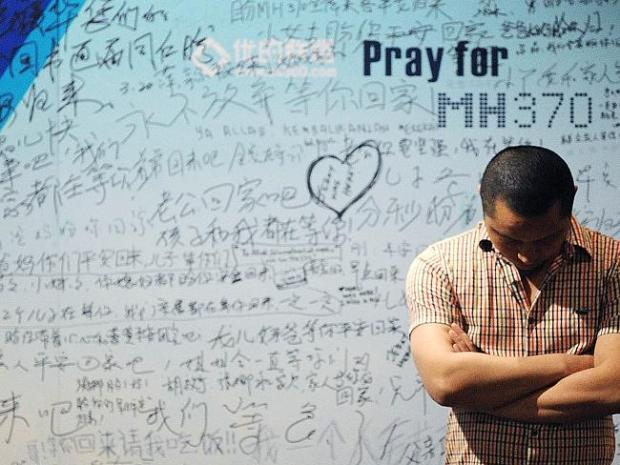 Sombre ... A man stands in front of a billboard in support of missing Malaysia Airlines f