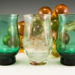 Mold blown retro glass vase set can double as candle votives or tumblers. Includes two Pine Green and one colorless with pine cone etching.