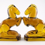 Vintage glass horse bookends in lovely and amber. The thick caramel colored glass changes in intensity according to the varying thickness of the glass and the lighting conditions, much like the real amber gem.