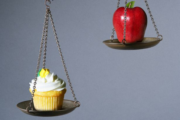 Scale weighing the value of a cupcake and apple