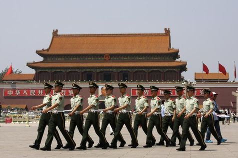 523981-paramilitary-police-walk-past-portrait-of-former-chinese-chairman-mao-at-tiananmen-square-in-beijing