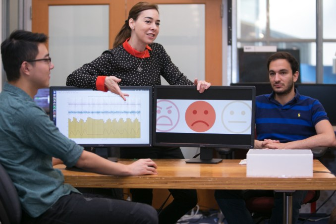 Professor Dina Katabi (middle) explains how PhD Fadel Adib's face (right) is neutral, but that EQ-Radio's analysis of his heartbeat and breathing show that he is sad. Credit: Jason Dorfman MIT CSAIL