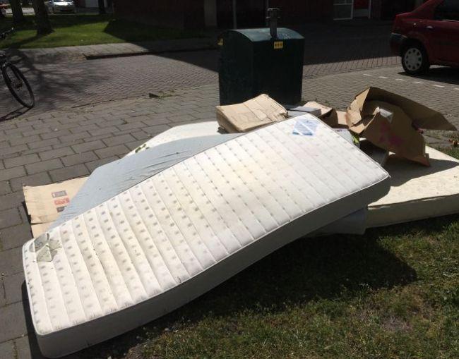 Kartonnen dozen en matrassen bij de afvalcontainer (foto Suzanne Rijnja)