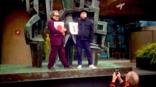 Roofboek kopers Peter Mertens & Harold Schellinx met knielende kalende fotograaf/uitgever Jaap Holtzapffel voor de Zadkine sculptuur bij De Nederlandsche Bank, Frederiksplein, Amsterdam (foto Facebook)