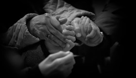 Close-Up Of People Praying By Holding Hands