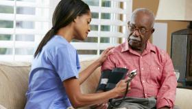 Nurse Visiting Senior Male Patient At Home