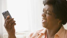 Senior African woman yelling at cell phone
