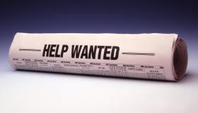 Rolled newspaper titled help wanted, close-up
