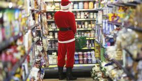 Man dressed as Santa Claus standing in supermarket, rear view