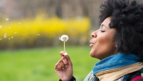 Black woman blowing dandelion seeds in park