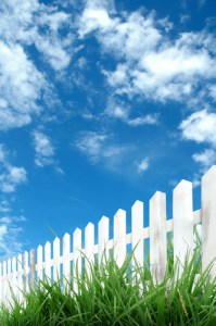 white_fence_with_green_grass_and_blue_sky
