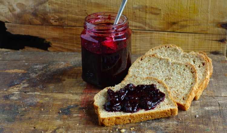 Bread topped with glossy dark burgundy jam.