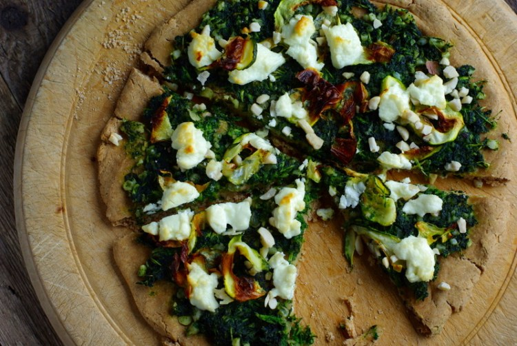 Golden flatbread with dark green pesto and lumps of browned goat's cheese