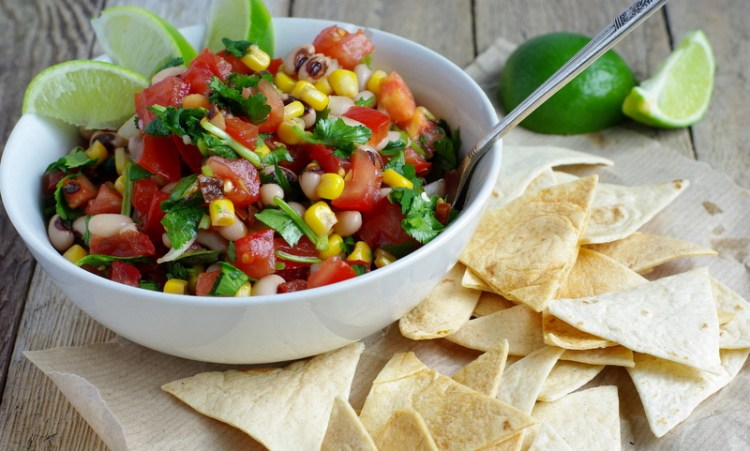 A vibrant, colourful bowl of fresh salsa with black eyed beans throughout and baked tortilla chips.