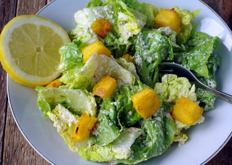 Crisp ceasar salad with golden croutons and a slice of lemon