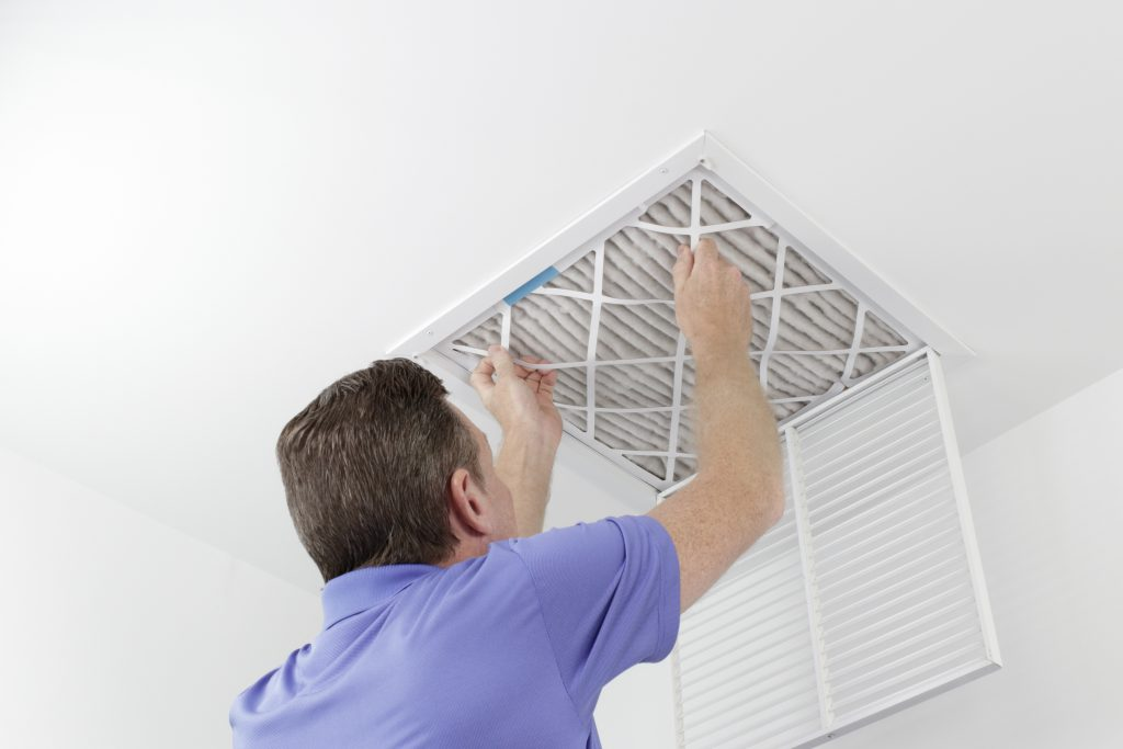 Caucasian male removing a square pleated dirty air filter with both hands from a ceiling air duct. Cleaning your air conditioning system will keep pollen out of your house during allergy season.
