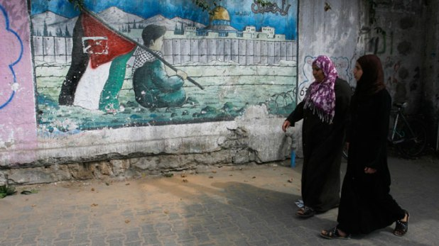 Palestinian women walk past a mural on the theme of return of refugees to their land in what is now Israel in the southern Gaza Strip refugee camp of Rafah on May 8, 2012.(AFP Photo / Said Khatib)