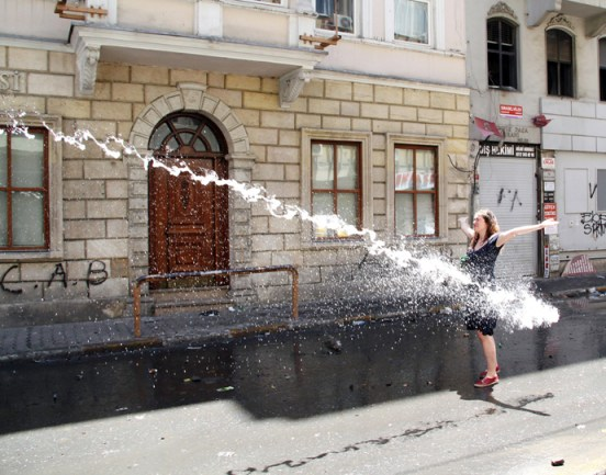 A woman opens her arms as police use a water cannon to disperse protestors on June 1, 2013 during a protest against the demolition of Taksim Gezi Park in Istanbul (AFP Photo)