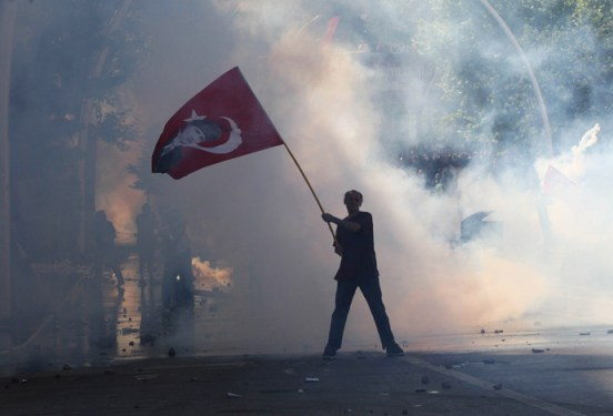 Tear gas surrounds a protestor holding a Turkish flag with a portrait of the founder of modern Turkey Mustafa Kemal Ataturk as he takes part in a demonstration in support of protests in Istanbul and against the Turkish Prime Minister and his ruling Justice and Development Party (AKP), in Ankara, on June 1, 2013 (AFP Photo / Adem Altan)