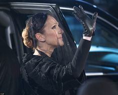 Farewell: Celine waves to the fans that turned out to show support for the singer in her time of grief as she departs the funeral