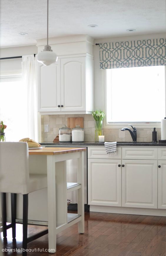 A modern farmhouse kitchen boasts classic white cabinets, open shelving and a soothing neutral color palette | A Burst of Beautiful: