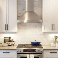 White cabinets with tile marble backsplash, stainless ...