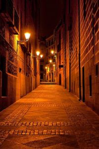 Narrow alley illuminated by street lamps at night, Madrid ...