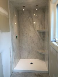 A subtle grey Marble-ite shower paired with a bright white ...