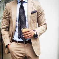 Tan suit, light blue shirt, navy tie with medallions ...