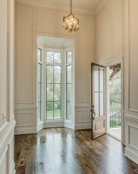Chic foyer features tall ceilings over full wall ...