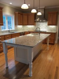 White kitchen island with granite countertop and prep sink ...
