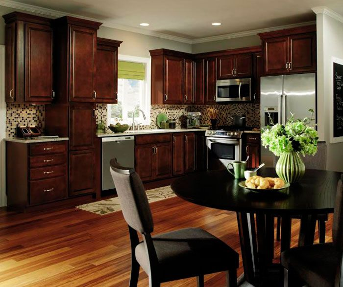 Dark wood kitchen cabinets are punctuated by stainless