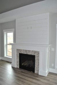 White shiplap fireplace, with perfectly-placed outlets for ...