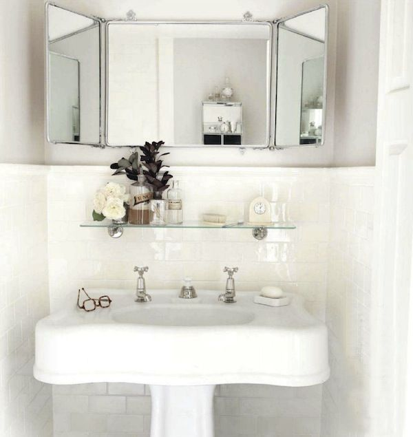Chic small powder room with glossy white pedestal sink