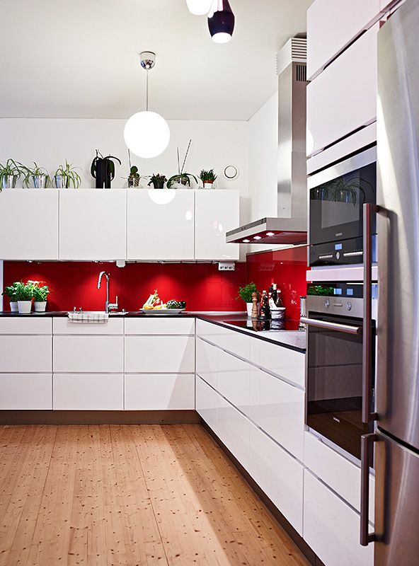 Red splashback white cabinets silver appliances and wooden