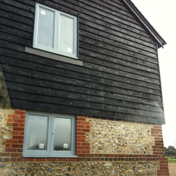 black barn board cladding with brick and flint and grey
