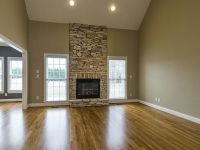 Floor to ceiling stacked stone fireplace flanked by ...