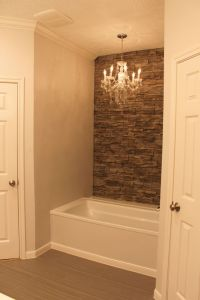 My tub with faux stone wall accent wall and chandelier