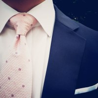 Blush pink tie paired with dark blue suit and white pocket ...