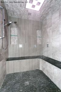 A modern walk in shower with a large shower bench and ...
