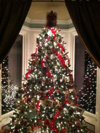 Christmas tree w velvet ribbons, collected ornaments and ...