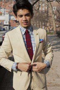 Tan suit, plaid shirt, red knit tie with blue stripes ...
