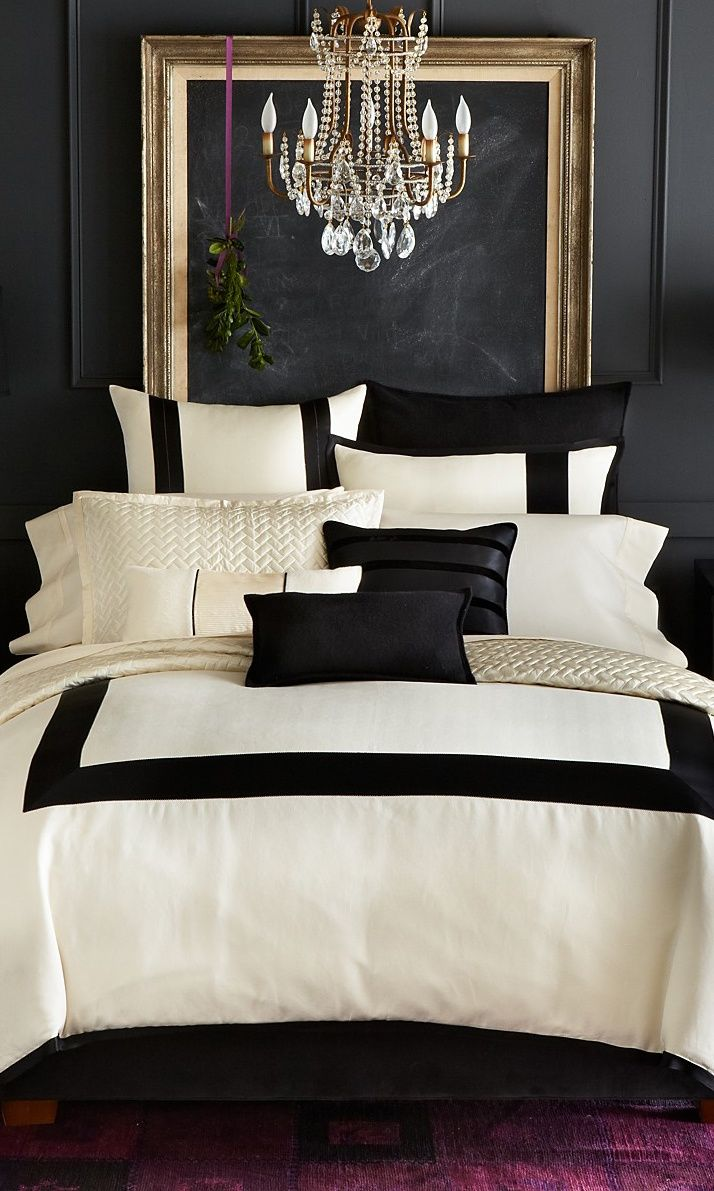 Super sophisticated luxurious cream and black bedding against a pure black wall with gold framed blackboard purple carpet and ribbon with mistletoe hung