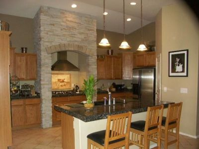 2000s kitchen Phoenix homes Design Through the Decades - stacked stone surrounding cook top ...
