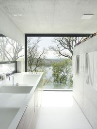 A large, fixed bathroom window creating a panoramic view ...