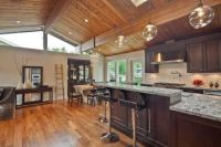 Kitchen with wood paneled, vaulted ceiling and skylight ...